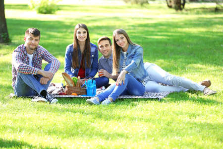 Happy friends on picnic in park