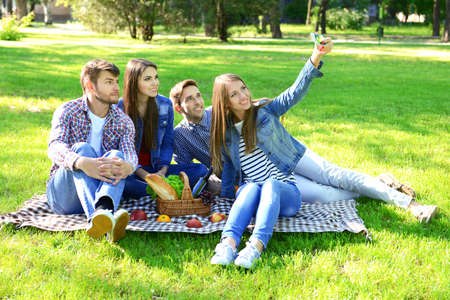 picnicking: Happy friends on picnic in park