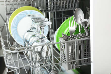 Open dishwasher with clean utensils in it photo