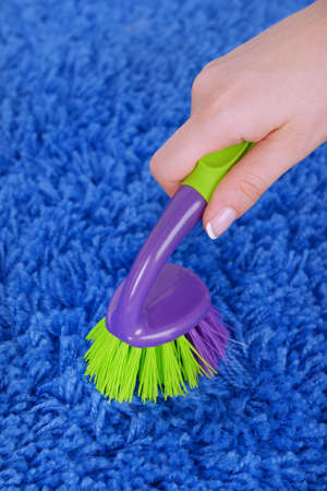 Cleaning carpet with brush close up photo