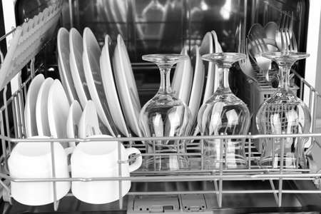 clean dishes: Open dishwasher with clean utensils in it