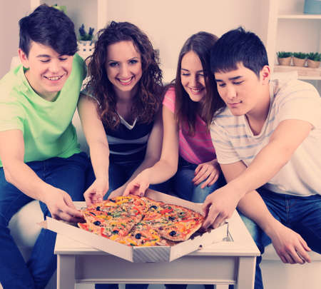 eating pizza: Group of young friends eating pizza in living-room on sofa Stock Photo