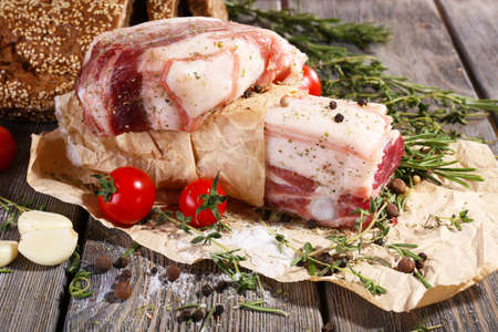 belly pepper: raw bacon with spices and tomatoes on wooden table