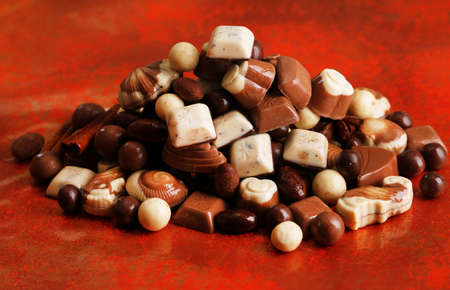 Different kinds of chocolates on red background photo