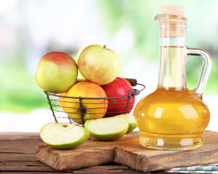 Apple cider vinegar in glass bottle and ripe fresh apples, on wooden table, on nature background photo