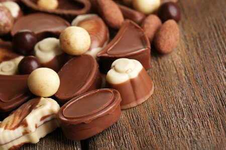 Different kinds of chocolates on wooden table close-up photo