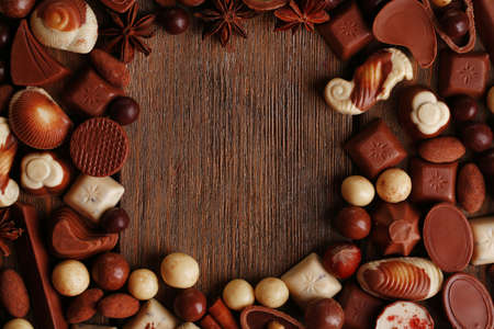 Frame of different kinds of chocolates on wooden table close-up photo