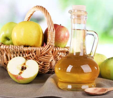 El vinagre de manzana en botella de vidrio y manzanas frescas maduras, en mesa de madera, en el fondo la naturaleza Foto de archivo - 32593660