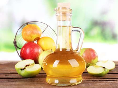 El vinagre de manzana en botella de vidrio y manzanas frescas maduras, en mesa de madera, sobre fondo de naturaleza