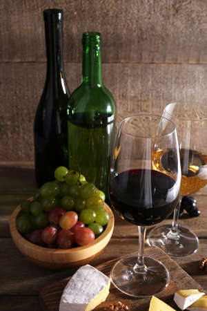 beautiful still life with wine, cheese and ripe grape on wooden background photo