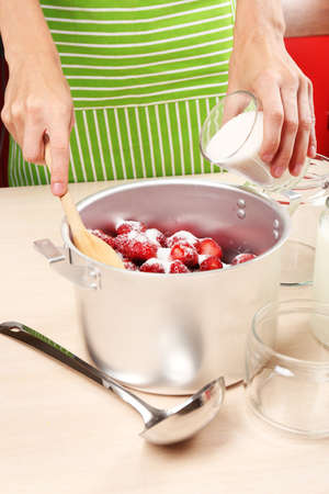 Het koken van heerlijke aardbeijam in keuken