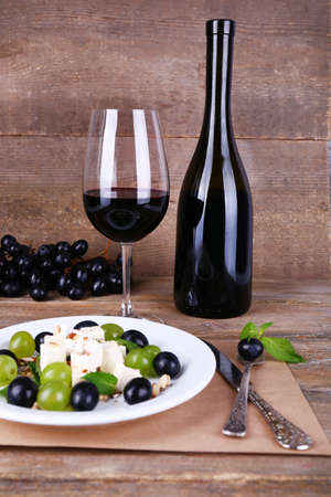 beautiful still life with wine and salad on wooden background photo