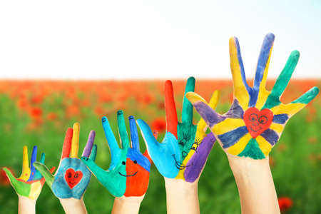 painted hands: Painted hands on field background Stock Photo