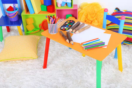 nurser: Interior of classroom at school, Crayons and paper on table Stock Photo