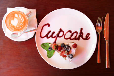 Cup of coffee and tasty cupcake on table in cafe photo