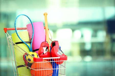 equipos: Concepto de compras. Carro de compras con equipamiento deportivo en la tienda de fondo