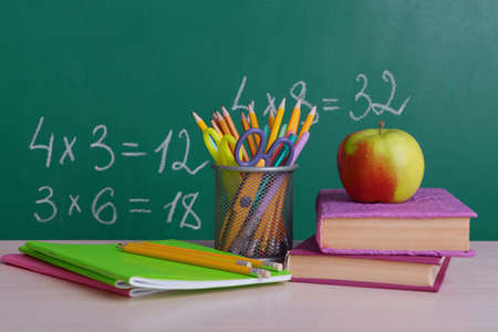 school time: School supplies on table on board background