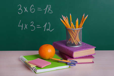 new school: School supplies on table on board background