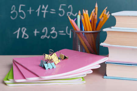 School supplies on table on board background photo