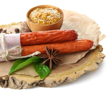 Smoked thin sausages, mustard in bowl and spices on wooden cutting board, isolated on white photo
