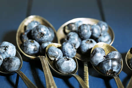 Tasty ripe blueberries in spoons, on wooden background photo