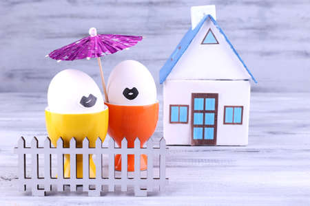 Eggs in egg cups near house and fence on grey wooden background photo