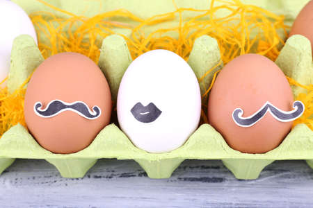 Eggs in cell egg tray on grey wooden background photo