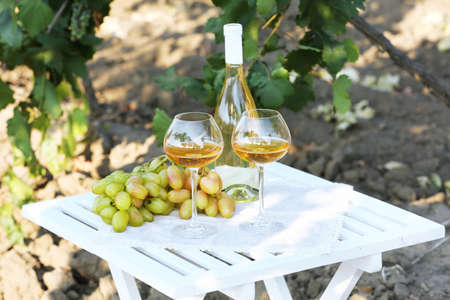 Ripe grape, bottle of wine and goblets on wooden table on grape bush background photo