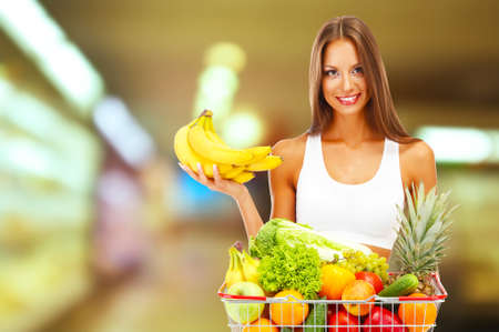 Beautiful young woman with fruits and vegetables in shopping basket on shop background photo