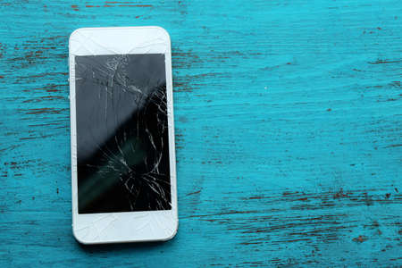 Modern mobile phone with broken screen on wooden background photo