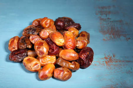 Tasty dates fruits on blue wooden table Stock Photo