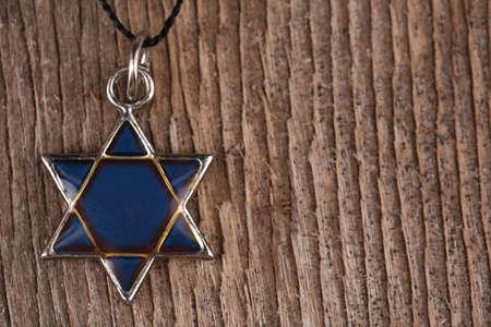 shield of david: Star David pendant on wooden background