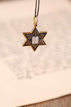 judah: Star David pendant on old paper page background
