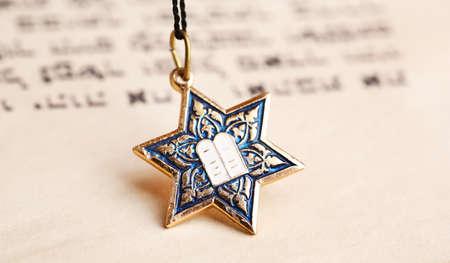 stella di davide: Stella pendente David sulla vecchia pagina di carta di sfondo Archivio Fotografico
