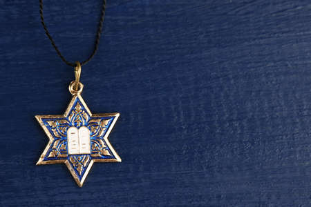 Star David pendant on wooden background photo