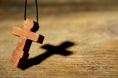 catholic symbol: Wooden cross with deep shadow on wooden background