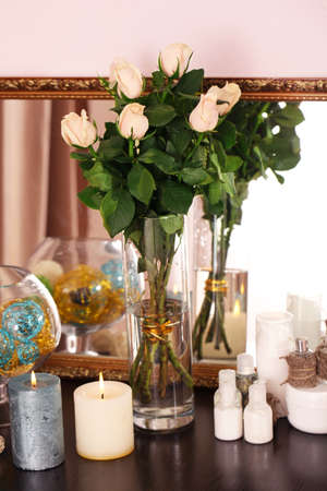 Beautiful vase with roses near mirror photo