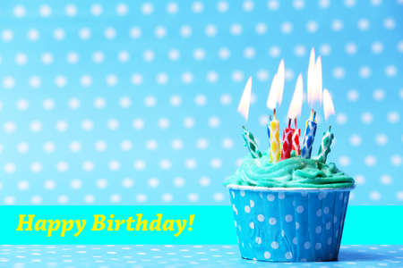 cup cake: Delicious birthday cupcake on blue background