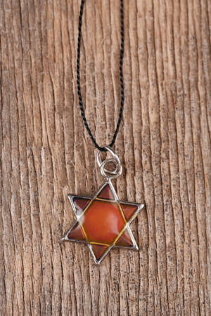 Star David pendant on wooden background photo