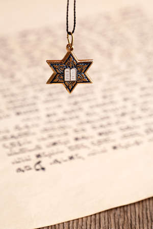 Star David pendant on old paper page background photo