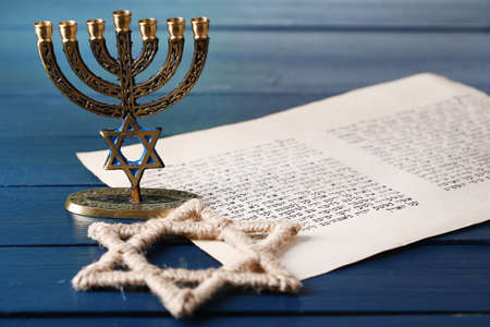 israelite: Menorah, star of David and page of Genesis book on wooden background