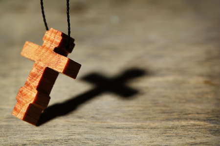 Croce di legno con profonda ombra su sfondo di legno Archivio Fotografico