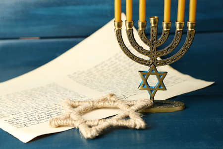 jewish star: Menorah, star of David and page of Genesis book on wooden background