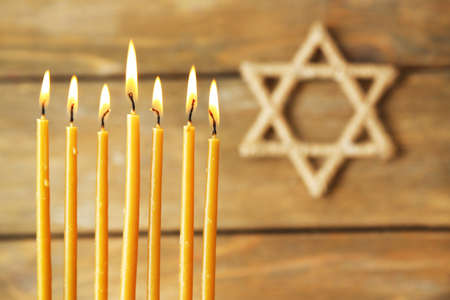 Hanukkah candle on wooden background photo