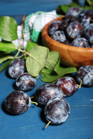 Ripe sweet plums in bowl, on wooden table photo