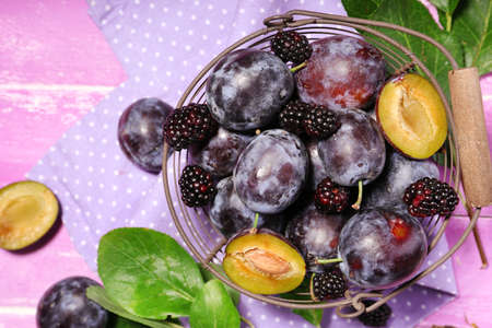 Ripe sweet plums in old metal basket, on pink wooden table photo