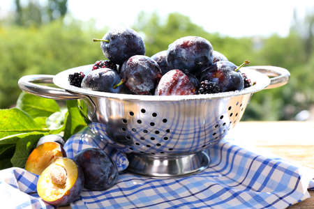 Ripe sweet plums in metal colander, on  nature background photo