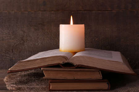 Books and candle on napkin on wooden table on wooden wall background photo