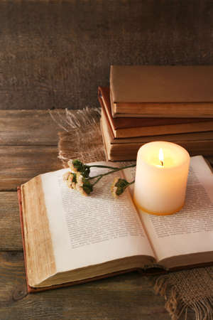 Books, flowers and candle on napkin on wooden table on wooden wall background photo