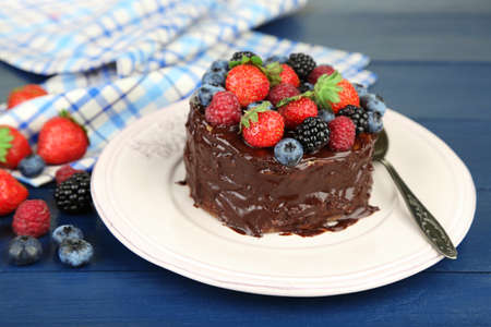 home made: Tasty chocolate cake with different berries, on wooden table